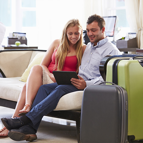 Couple in hotel using the self check-in option of Clock PMS Suite to skip the line at Reception